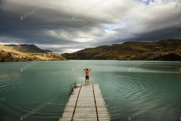 Un joven de pie al final de un muelle de madera en un lago en el Parque Nacional Torres del Paine, Chile.