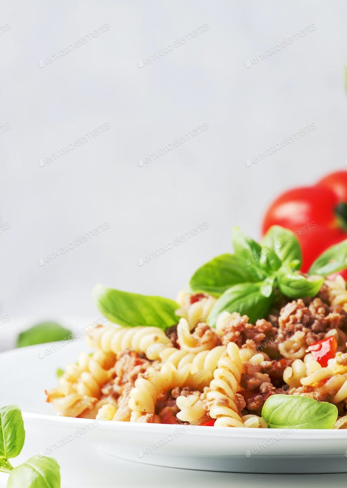 Prepared pasta with meat sauce with tomatoes and basil