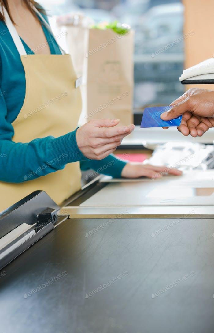 Kunde übergibt einem Vertriebsassistenten eine Kreditkarte