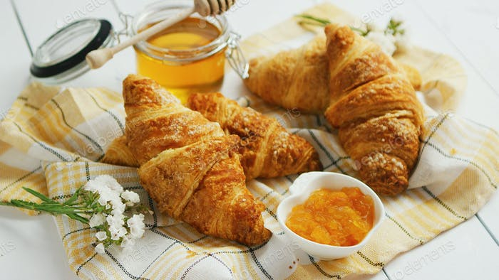 Condiments and croissants lying on towel