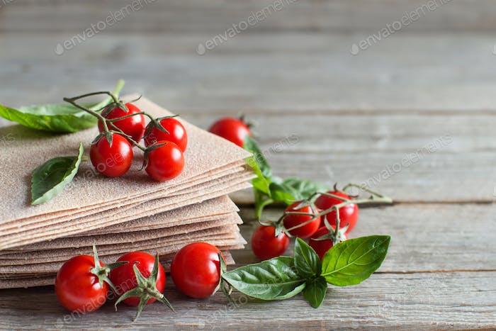 Raw lasagna sheets,basil and cherry tomatoes