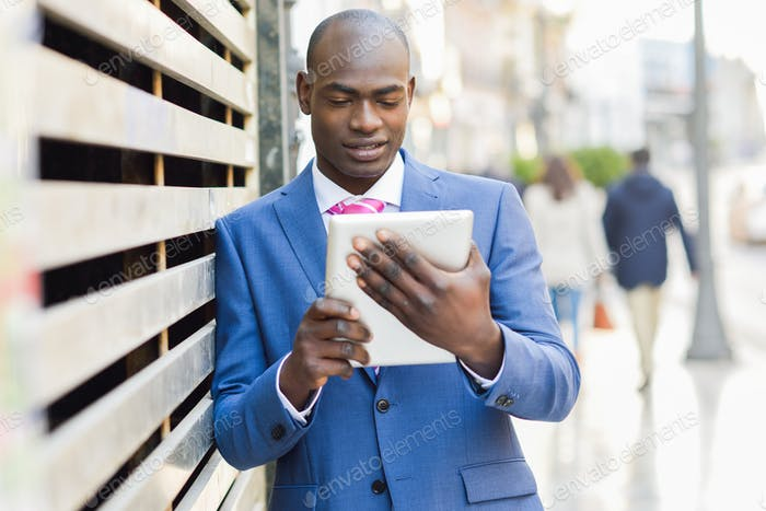 Black businessman using digital tablet in urban background
