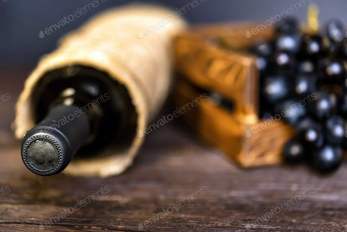 Bottle of red wine and grapes on wooden surface