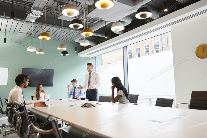 Mature Businessman Giving Boardroom Presentation To Colleagues In Meeting Room