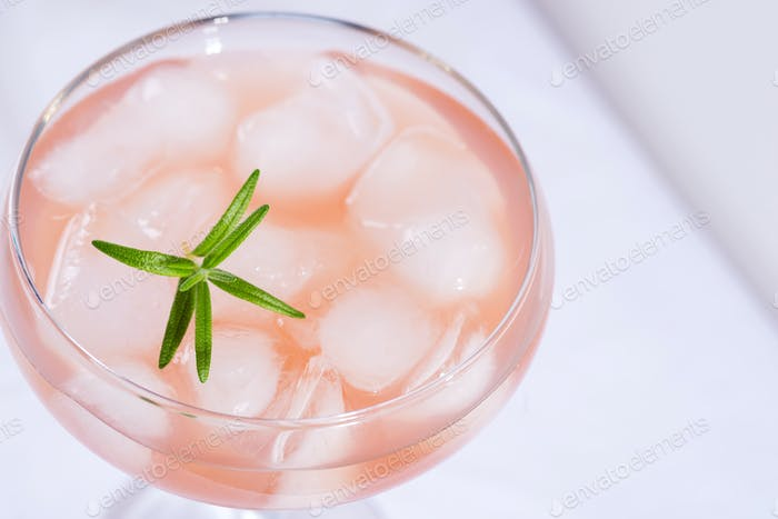 Pink cocktail with rosemary and ice on a white tablecloth close-up