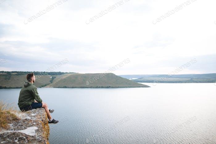 Hipster Reisende sitzt auf dem Felsenberg und genießt einen atemberaubenden Blick auf den Fluss