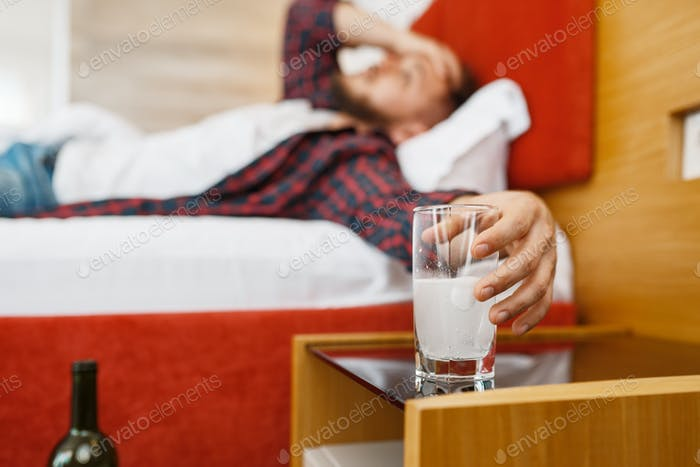 Hangover man holding a glass with soluble tablet