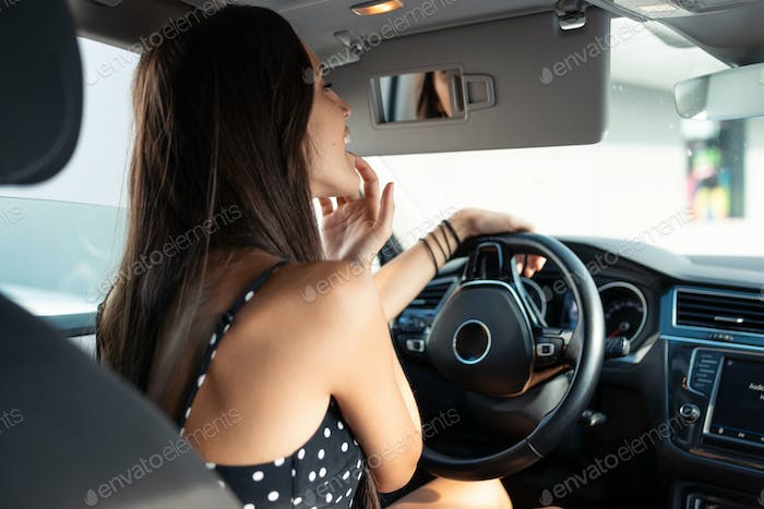 Beautiful young woman applying lip balm while looking in rearview mirror in the car.