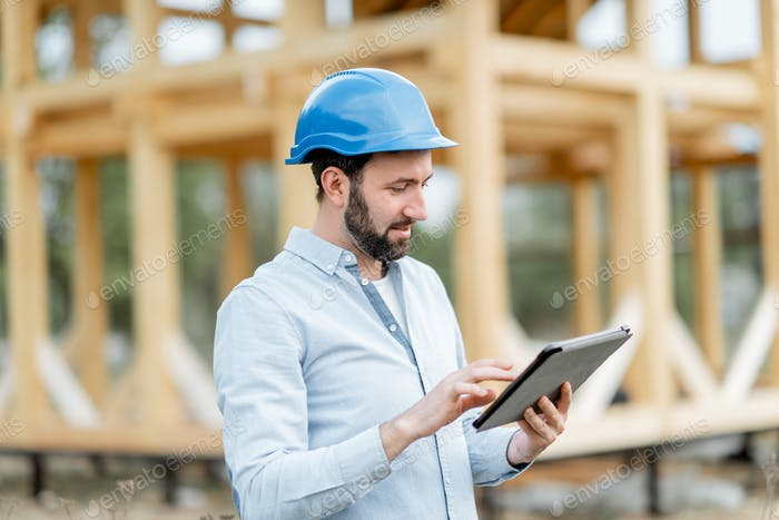 Builder with digital touchpad near the wooden house on the construction site