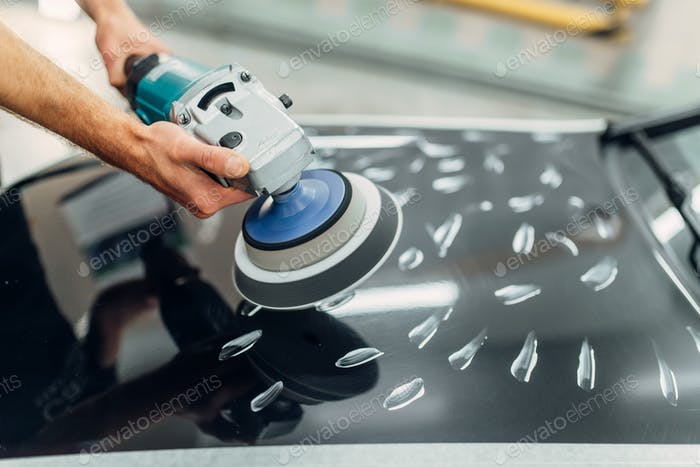 Worker with polishing machine cleans car hood