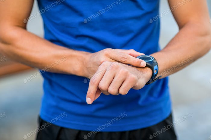 An handsome athlete looking at his watch on a sunny day