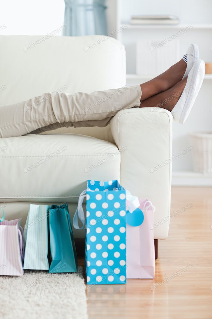 Woman on couch putting her feet up