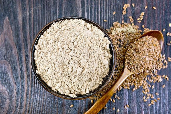 Flour linen in bowl with seeds in spoon on board top