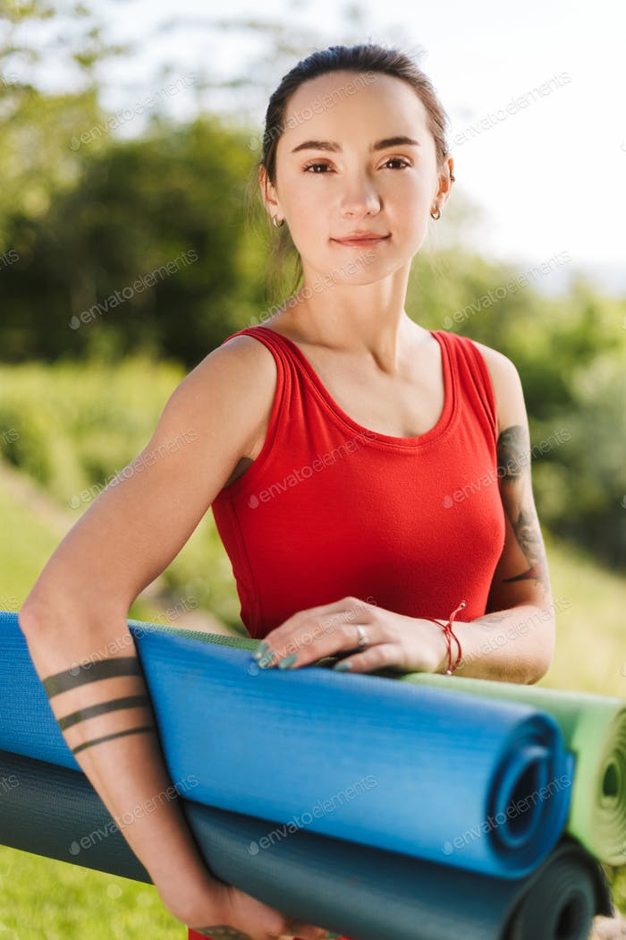 Portrait of young beautiful yoga trainer in red jumpsuit standing with yoga mats in hands