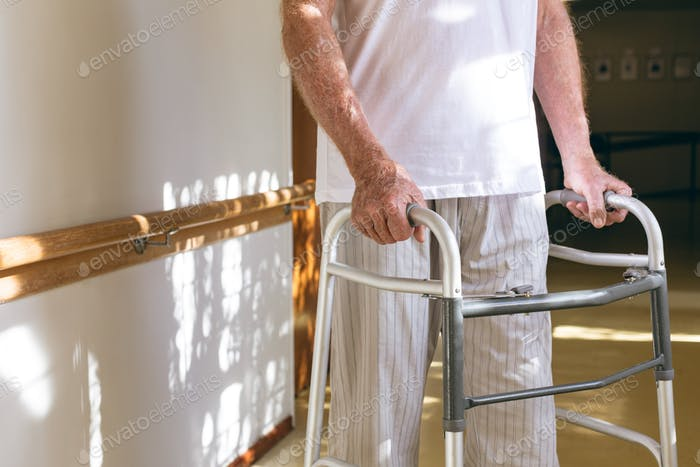 Mid section of senior Caucasian male patient standing with walker in corridor at retirement home