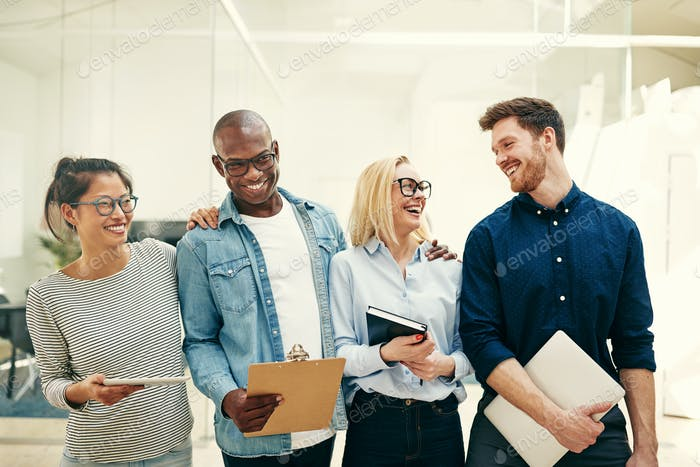 Group of diverse young businesspeople laughing together in an office