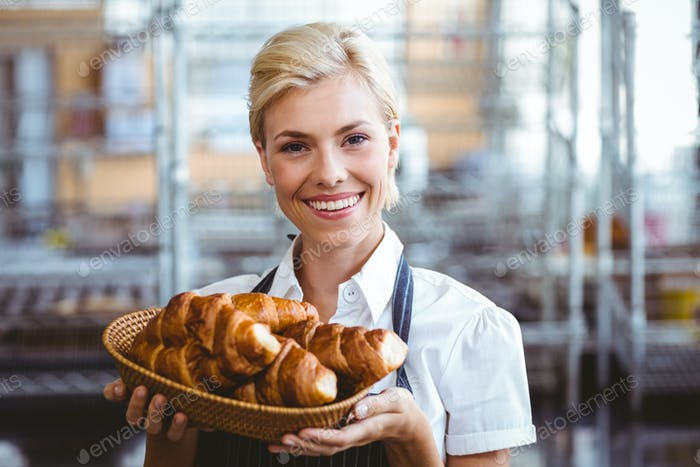 Cheerful gorgeous waitress holding a basket with croissant in the bakery