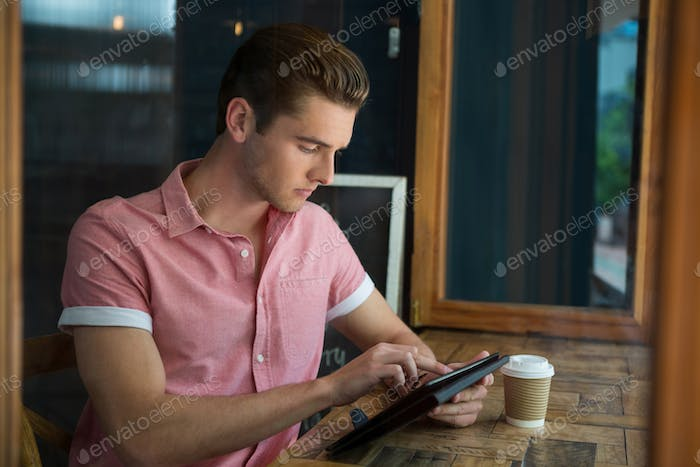 Man using digital tablet at table in coffee shop