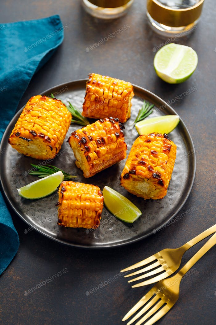 Roasted or grill corn cob with olive oil and salt on a black plate.