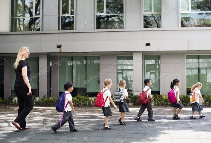 Kindergarten students walking crossing school road
