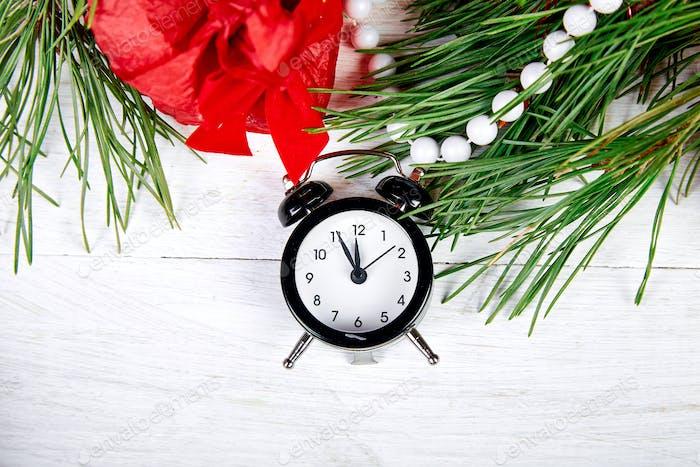 Schwarzer Wecker und Tannenzweig, rote Weihnachtsdekoration