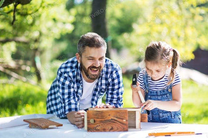 Vater mit einer kleinen Tochter draußen, Herstellung hölzerner Vogelhaus.