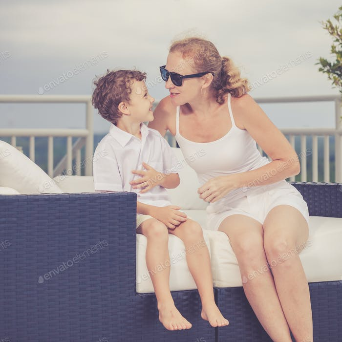 Mother and son relaxing near a swimming pool  at the day time.