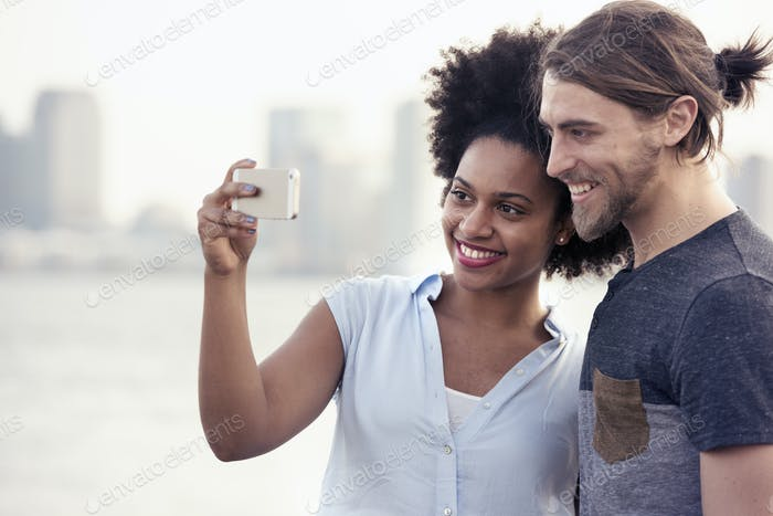 A couple, man and woman taking a selfie by the waterfront in a city