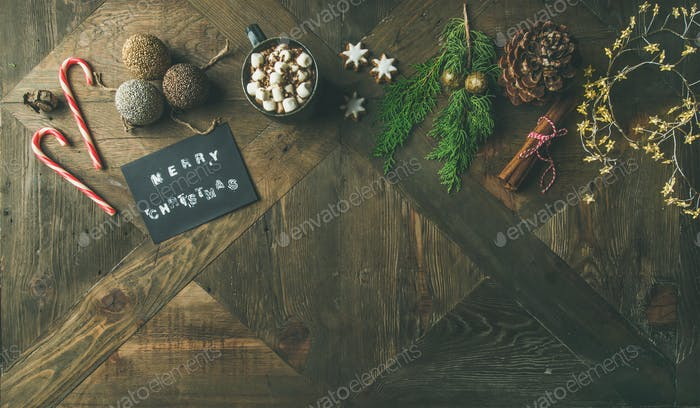 Flat-lay of greeting card, mug of hot chocolate, candy cane