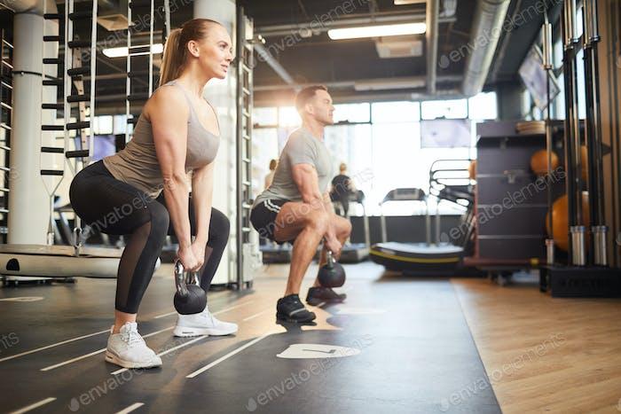 paar tun Kniebeugen mit Gewichten
