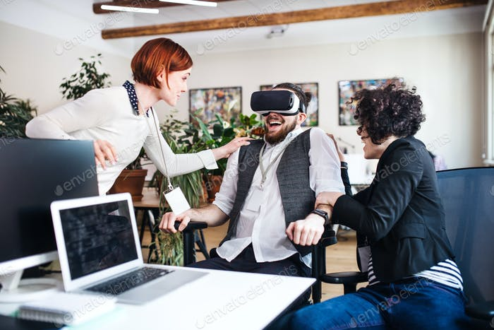Group of young businesspeople with VR goggles talking in office, start-up concept