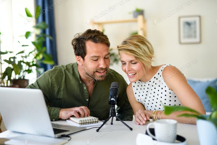 Happy couple with microphone having video call on laptop indoors at home