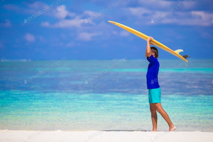 Happy young surf man at white beach with yellow surfboard