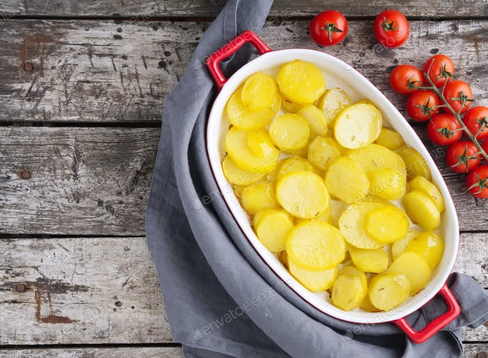 Baked slice of potatos, healthy diet food. Dark old wooden rustic gray background, top view