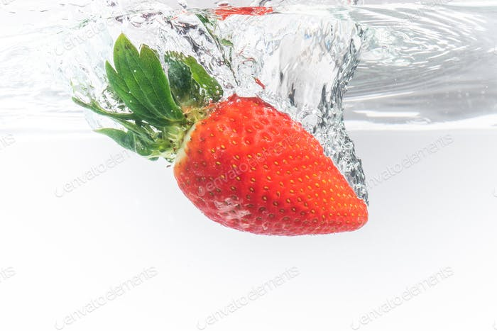 Fresh strawberry dropped into clear water with splash isolated on white background