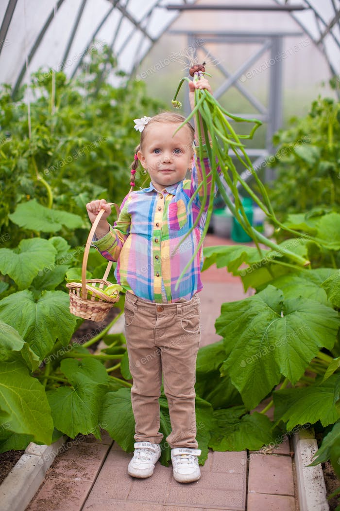 Little adorable girl holding the crop onions in greenhouse