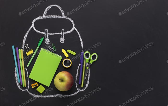 Green school stationery inside chalk painted backpack on black