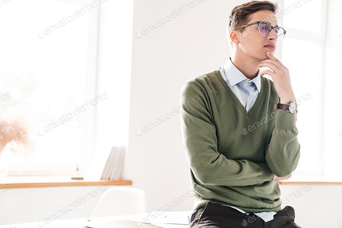 Thoughtful young guy student sit on table