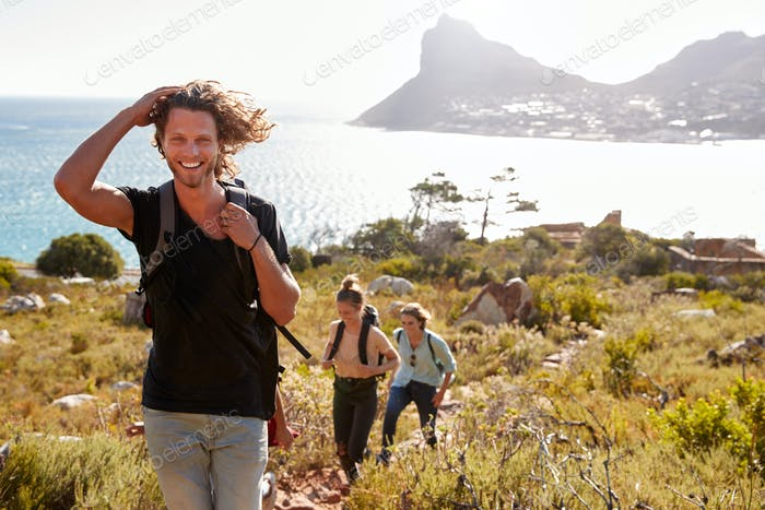 Young adult white man hiking with friends in countryside by the coast smiling to camera