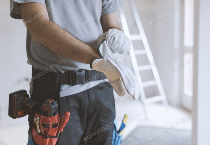 Professional repairman wearing protective gloves