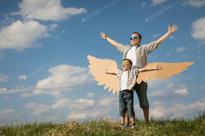 Vater und Sohn spielen mit Pappe Spielzeug Flügel