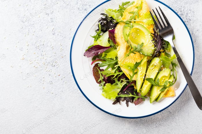 Breakfast green omelet, salad mix and avocado. Concept Healthy food in the morning.