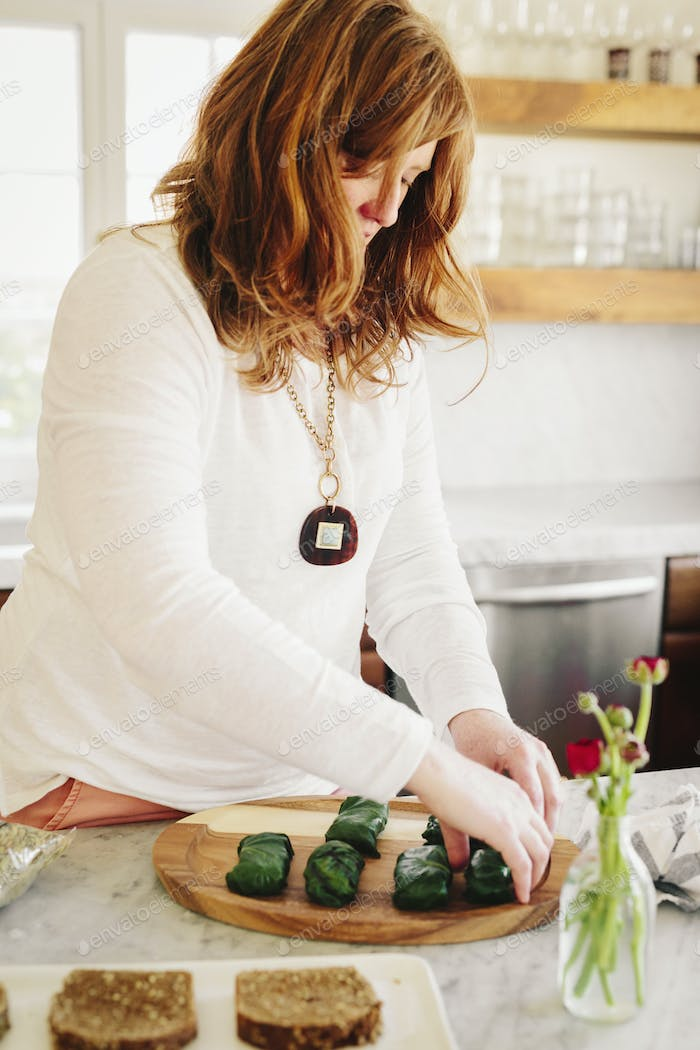 A woman preparing stuffed vine leaves as a lunch dish in a kitchen.