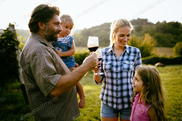 Winemaker family together in vineyard tasting vine