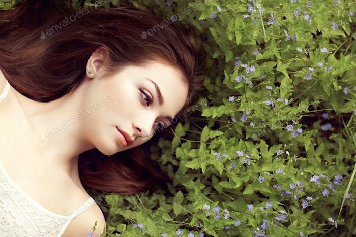Vertical de una hermosa Mujer joven en verano jardín