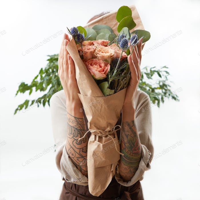 Wonderful bouquet from coral color roses and eryngium in girl's hands on a light background with