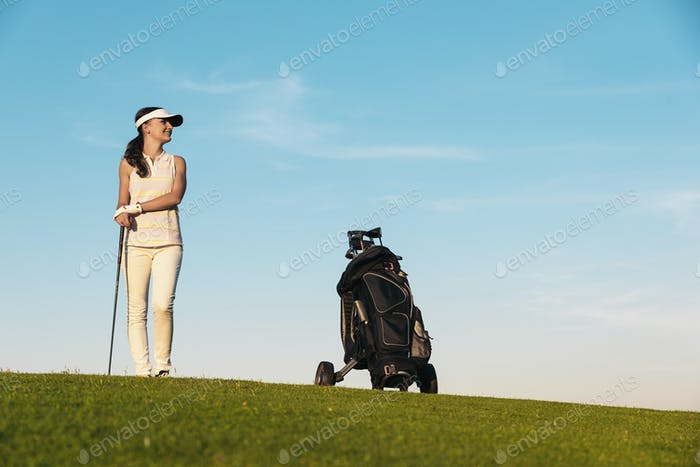 Pretty young woman playing golf.