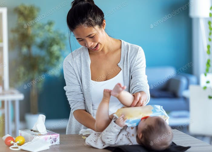 Smiling young mother has fun with little baby while changing his nappy at home.