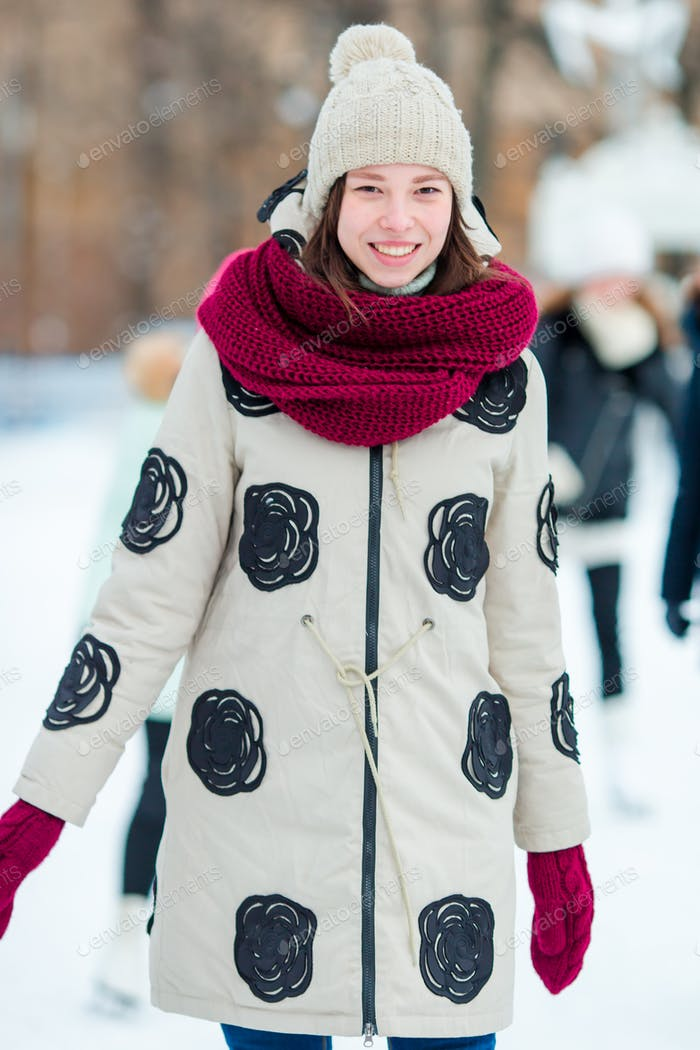 Happy young woman skating on ice rink outdoors
