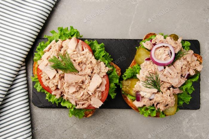 Flacher Blick auf Thunfisch-Sandwiches mit Salat Tomaten Gurken und Zwiebeln auf Schieferplatte